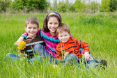 Three smiling kids on green meadow — Stockfoto