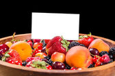 Fresh berries in plate with blank card — Stock Photo