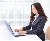 Przemyślany biznes kobieta w biurze laptop z uśmiechem. — Zdjęcie stockowe
