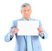 Nice businessman at the age of't holding a big white poster. Isolated on a white background. — Stock Photo