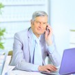 The businessman at the age of works for the laptop. — Stock Photo