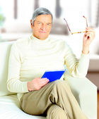 Senior man relaxing at home with a book — Stock Photo