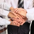 Stock Photo: Business team putting their hands on top of each other