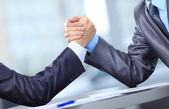 Two businessmen press hands each other on a forward background — Stock Photo