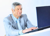 The businessman at the age of works for the laptop. Isolated on a white background. — Stock Photo