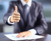 A businessman in the office of the shows his thumb on top. — Stock Photo