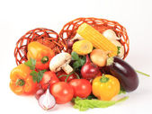 Composition with raw vegetables and wicker basket isolated on wh — Stockfoto