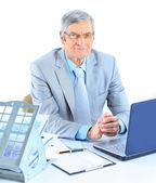 L'uomo d'affari all'età delle opere per il laptop. isolato su sfondo bianco. — Foto Stock