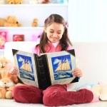 encantadora niña leyendo el libro con su juguete en sofá blanco — Foto de Stock