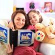 Happy mother and daughter reading a book together — Stock Photo