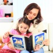 Happy mother and daughter reading a book together — Stock Photo #21587461