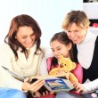 Grandmother, mother, and daughter reading a book together — Stock Photo #21587621