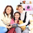 Grandmother, mother, and daughter reading a book together — Foto Stock