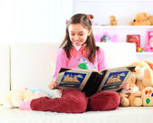 Charming little girl reading book with her toy on white sofa — Stock Photo