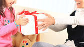 Little beautiful pretty girl giving a gift to her happy mother — Stock Photo