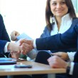 Stock Photo: Mature businessman shaking hands to seal a deal with his partner and colleagues in a modern office