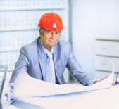 Engineer at the age of considering plans drawing and corrects them. — Stock Photo