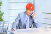 Engineer at the age of talking on the phone about the plans of the drawing. — Stock Photo