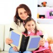 Happy mother and daughter reading a book together — Stock Photo #22144185