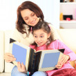 Happy mother and daughter reading a book together — Stock Photo #22144271