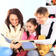 Grandmother, mother, and daughter reading a book together — Stock Photo