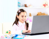 Cute little girl smiling and looking at laptop,Little girl using laptop — Stock Photo
