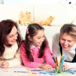 Beautiful girl draws with his mother and aunt. — Stock Photo #23530141