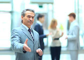 Welcoming business man ready to handshake with hand extended — Stock Photo