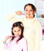 Mother and daughter brush their teeth. — Stock Photo