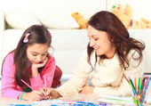Beautiful girl draws with his mother — Stock Photo
