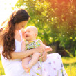 Stock Photo: Beautiful Mother And Baby outdoors. Nature. Beauty Mum and her Child playing in Park together
