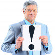 Nice businessman at the age, with an exclamation mark. Isolated on a white background. — Stock Photo