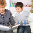 Stock Photo: Grandmother and grandson reading a book