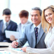 Smiling business people with paper work in board room — ストック写真