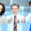 Three business partners keeping thumbs up — Foto de Stock