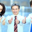 Three business partners keeping thumbs up — Stockfoto