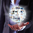 Business woman holding a ball of people on a dark background — Stock Photo