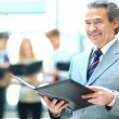 Successful business man standing with his staff in background at office — Stockfoto