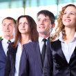 Group of friendly businesspeople with happy female leader in front — Stock Photo