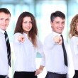 Group of four business people in a row pointing — Stock Photo