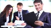 Succesvolle business man die met zijn personeel in de achtergrond op kantoor — Stockfoto