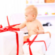 Adorable baby girl with gift boxes posing over on the couch — Stok fotoğraf