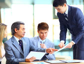 Business team interviewing young applicant in bright office — Stock Photo