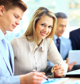 Smiling businesswoman posing while colleagues talking together in bright office — Fotografia Stock