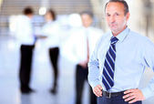 Happy mature business man looking at camera with satisfaction at office — Stock Photo