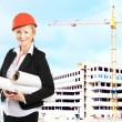 Young female construction specialist reviewing blueprints at construction site — Stock Photo #42878237