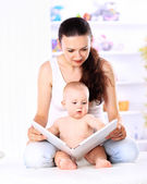 Charming mother showing images in a book to her cute little son at home — Stock Photo