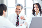 Successful businessteam of three sitting in office and planning work — Stock Photo