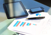 Financial charts on the table with tablet and pen — Stock Photo