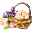 Easter eggs in a basket and spring flowers — Stock Photo